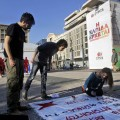 Young people affiliated with the radical left Greek main opposition party SYRIZA paint a banner outside a pre-election campaign stand of the party in central Athens, Greece, 17 January 2015. Greeks will vote on 25 January to decide for their next government. EPA/ ORESTIS PANAGIOTOU